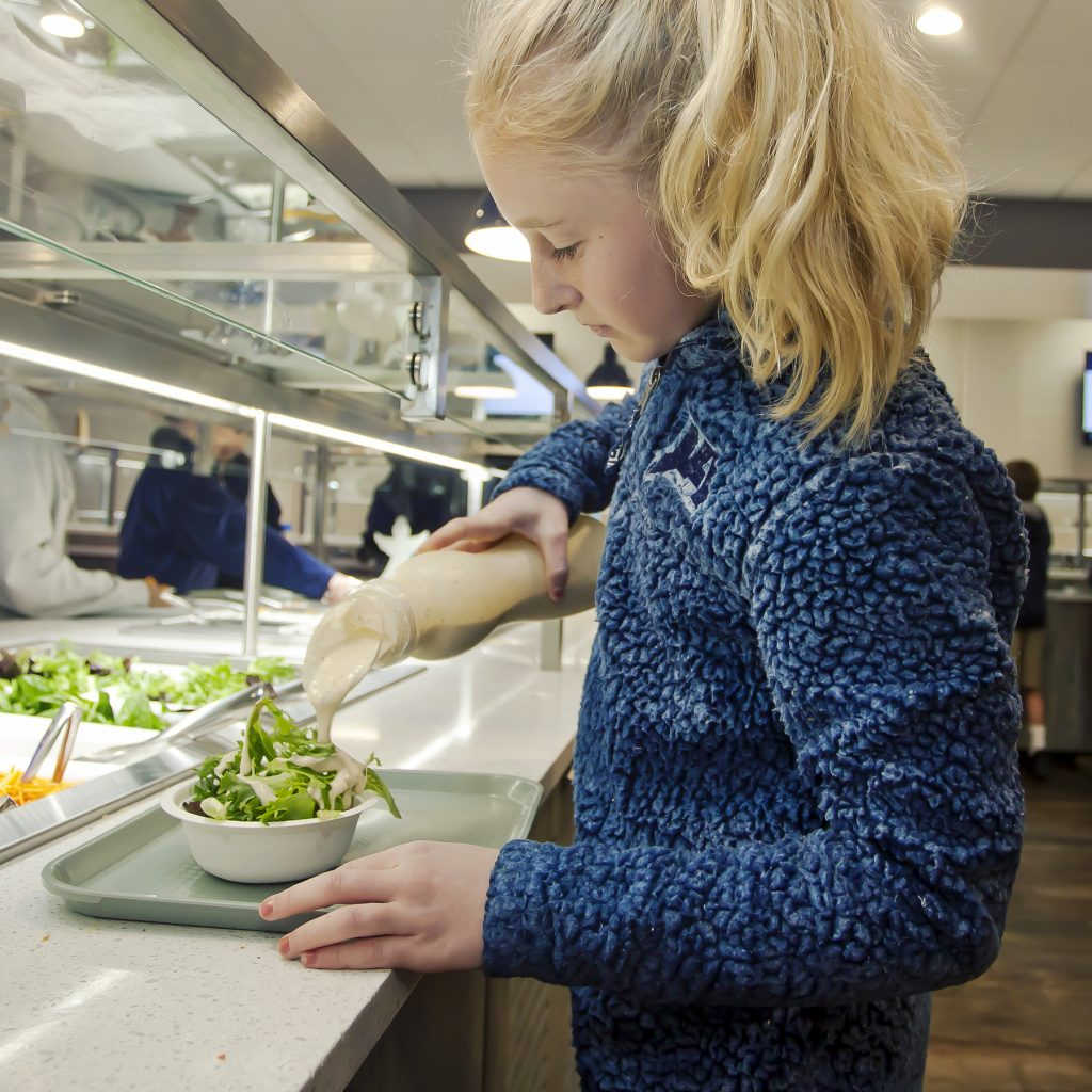 A middle school girl prepares a green salad at the salad bar of the newly-redesigned cafeteria that also features a fruit and yogurt bar.