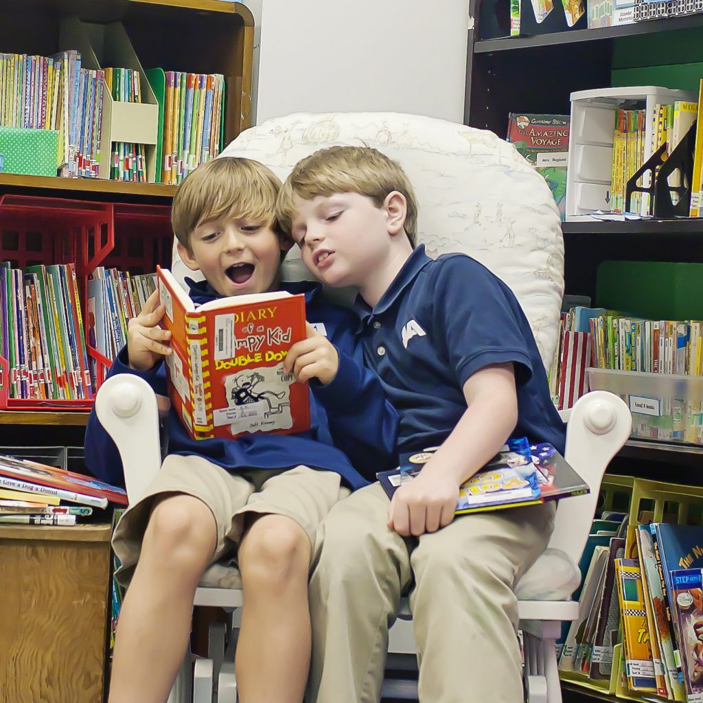 Two elementary age boys read a book together while sitting in a comfortable chair in the Lower School library.