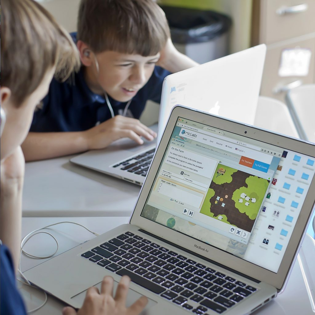 Two middle school age boys use Macbook Air computers while working on programs that teach coding, a skill valued in the workplace.