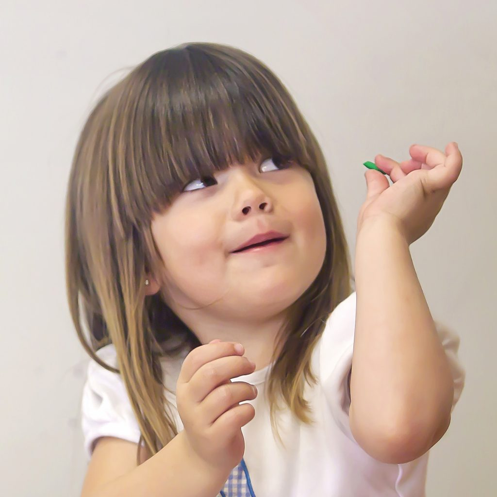 A three year old kindergarten student with brown hair looks up with a happy expression while holding a game piece that helps develop fine motor skills.