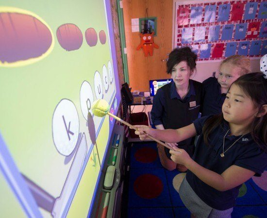 Teachers and students work together in front of a smart board