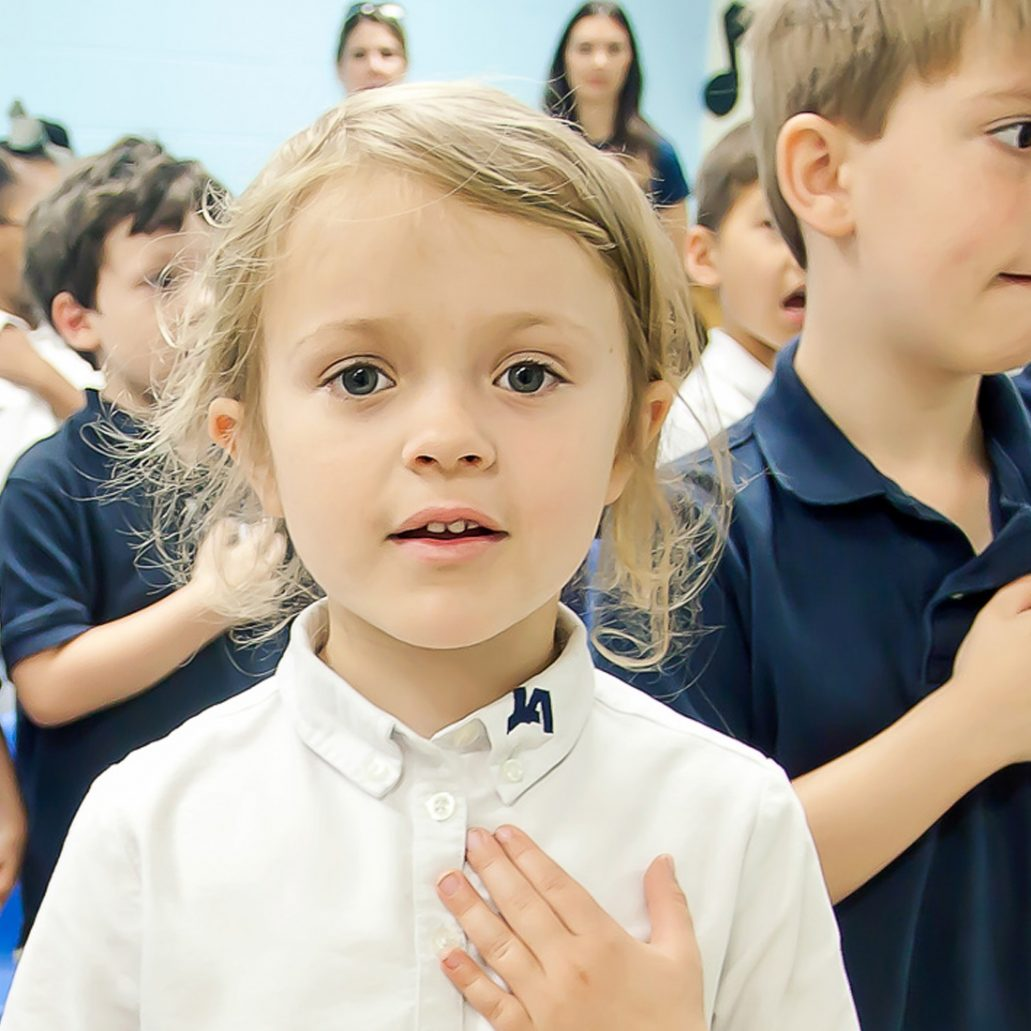 A kindergarten girl places her hand over her heart as she and her classmates recite the Pledge of Allegiance.